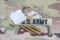 US ARMY branch tape with dog tag and 5.56 mm rounds on camouflage uniform. Background Stock Photography