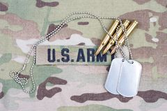 US ARMY branch tape with dog tag and 5.56 mm rounds. On camouflage uniform Royalty Free Stock Photo