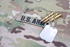 US ARMY branch tape with dog tag and 5.56 mm rounds on camouflage uniform. Background royalty free stock photography