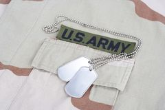 US ARMY branch tape with dog tags on desert camouflage uniform. Background Royalty Free Stock Images