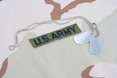 US ARMY branch tape with dog tags on desert camouflage uniform. Background Royalty Free Stock Image