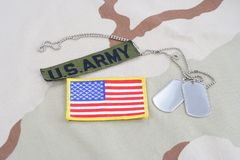 US ARMY branch tape with dog tags and flag patch on desert camouflage uniform. Background Stock Photography