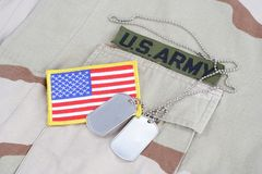 US ARMY branch tape with dog tags and flag patch on desert camouflage uniform Royalty Free Stock Images