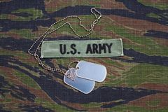 US ARMY branch tape and dog tags on tiger stripe camouflage uniform. Background Royalty Free Stock Photos