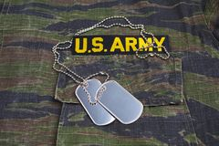 US ARMY branch tape and dog tags on tiger stripe camouflage uniform. Background Stock Images
