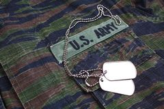 US ARMY branch tape and dog tags on tiger stripe camouflage uniform. Background Royalty Free Stock Photography