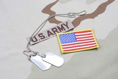 US ARMY branch tape with dog tags a. Nd US flag patch on desert camouflage uniform background Stock Images