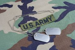US ARMY branch tape and dog tags on woodland camouflage uniform. Background Royalty Free Stock Photography