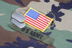 US ARMY branch tape, flag patch and dog tags on woodland camouflage uniform. Background Stock Image