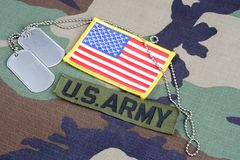 US ARMY branch tape, flag patch and dog tags on woodland camouflage uniform. Background Stock Photography