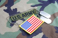 US ARMY branch tape, flag patch and dog tags on woodland camouflage uniform. Background Royalty Free Stock Image