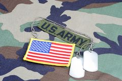 US ARMY branch tape, flag patch and dog tags on woodland camouflage uniform. Background Stock Photo
