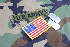US ARMY branch tape, flag patch and dog tags on woodland camouflage uniform. Background Royalty Free Stock Photography