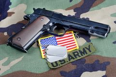 US ARMY branch tape, M1911 handgun with dog tags on woodland camouflage uniform. Background Stock Photography