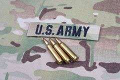 US ARMY branch tape and 5.56 mm rounds on camouflage uniform. Background Stock Photography