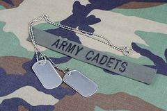 US ARMY CADETS branch tape and dog tags on woodland camouflage uniform. US ARMY CADETS  branch tape and dog tags on woodland camouflage uniform background Royalty Free Stock Image