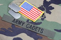 US ARMY CADETS branch tape, flag patch and dog tags on woodland camouflage uniform. Background Stock Photos