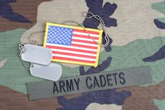 US ARMY CADETS branch tape, flag patch and dog tags on woodland camouflage uniform. Background Royalty Free Stock Photo