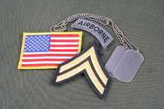 US ARMY Corporal rank patch, airborne tab, flag patch and dog tag on olive green uniform. Background royalty free stock photos