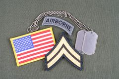 US ARMY Corporal rank patch, airborne tab, flag patch and dog tag on olive green uniform. Background Stock Photo