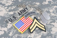 US ARMY Corporal rank patch, airborne tab, flag patch, with dog tags on camouflage uniform. Background Royalty Free Stock Photo