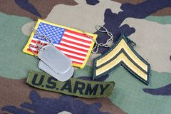 US ARMY Corporal rank patch, branch tape, flag patch and dog tags on woodland camouflage uniform. Background Royalty Free Stock Images