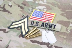 US ARMY Corporal rank patch, flag patch, with dog tag with 5.56 mm rounds on camouflage uniform. Background Royalty Free Stock Photo