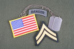 US ARMY Corporal rank patch, ranger tab, flag patch and dog tag on olive green uniform Royalty Free Stock Photography