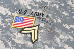 US ARMY Corporal rank patch, ranger tab, flag patch,  with dog tag on camouflage uniform Stock Image