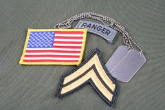 US ARMY Corporal rank patch, ranger tab, flag patch and dog tag on olive green uniform Royalty Free Stock Images