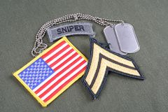 US ARMY Corporal rank patch, sniper tab, flag patch and dog tag on olive green uniform. Background Royalty Free Stock Photos