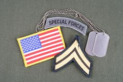US ARMY Corporal rank patch, special forces tab, flag patch and dog tag on olive green uniform. Background Stock Photos