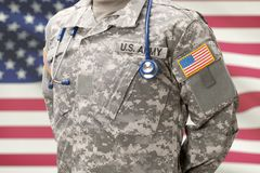 US Army doctor with stethoscope over his neck and USA flag on background stock photo