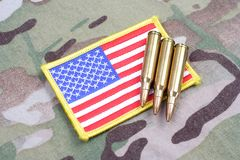 US ARMY flag patch and 5.56 mm rounds on camouflage uniform. Background Royalty Free Stock Photography