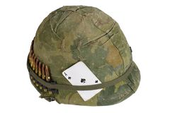 US Army helmet Vietnam war period with camouflage cover and ammo belt and amulet the ace of spades playing card. US Army helmet Vietnam war period with Royalty Free Stock Image