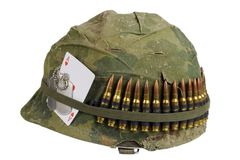 US Army helmet Vietnam war period with camouflage cover and ammo belt, dog tag and amulet ace of hearts playing card Stock Photos