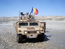 US Army Humvee drove by Romanians soldiers. Big US Army Humvee under Romanian patrol crossing a small river royalty free stock photos