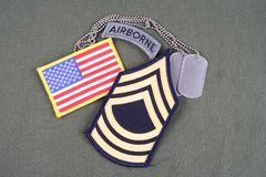 US ARMY Master Sergeant rank patch, airborne tab, flag patch and dog tag on olive green uniform. Background Royalty Free Stock Images