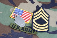 US ARMY Master Sergeant rank patch, branch tape, flag patch and dog tags on woodland camouflage unif. Orm background Stock Photos