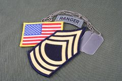 US ARMY Master Sergeant rank patch, ranger tab, flag patch and dog tag on olive green uniform Stock Photos
