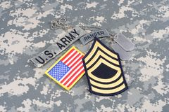 US ARMY Master Sergeant rank patch, ranger tab, flag patch,  with dog tag on camouflage uniform Stock Images