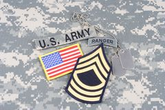 US ARMY Master Sergeant rank patch, ranger tab, flag patch,  with dog tag on camouflage uniform Stock Photography