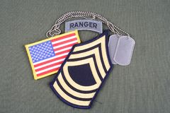 US ARMY Master Sergeant rank patch, ranger tab, flag patch and dog tag on olive green uniform Royalty Free Stock Images