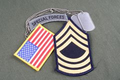 US ARMY Master Sergeant rank patch, special forces tab, flag patch and dog tag on olive green un. Iform background Royalty Free Stock Image