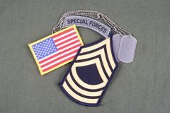 US ARMY Master Sergeant rank patch, special forces tab, flag patch and dog tag on olive green un. Iform background Stock Images