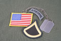 US ARMY Private First Class rank patch, airborne tab, flag patch and dog tag on olive green unif. Orm background Stock Image
