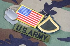 US ARMY Private First Class rank patch, branch tape, flag patch and dog tags on woodland camouflage. Uniform background Royalty Free Stock Photos