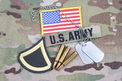 US ARMY Private First Class rank patch, flag patch, with dog tag with 5.56 mm rounds on camoufl. US ARMY Private First Class rank patch,  flag patch, with dog Royalty Free Stock Image