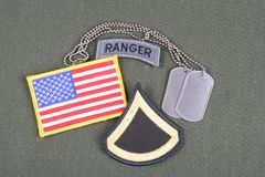 US ARMY Private First Class rank patch, ranger tab, flag patch and dog tag on olive green unifor Stock Photo