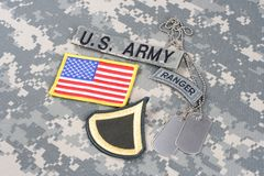 US ARMY Private First Class rank patch, ranger tab, flag patch,  with dog tag on camouflage unifo Stock Photography